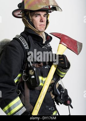 Male firefighter in structural firefighting uniform with breathing apparatus and axe - Stock Photo