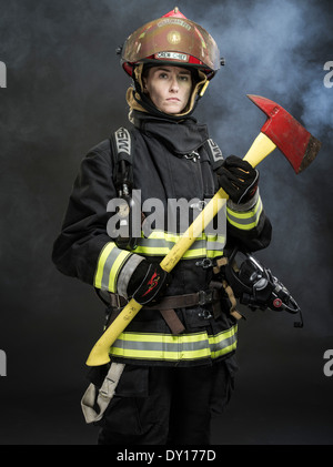 Female firefighter in structural firefighting uniform with breathing apparatus and axe - Stock Photo