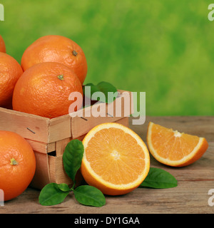 Freshly picked oranges with leaves in a wooden box on a table with green background - Stock Photo