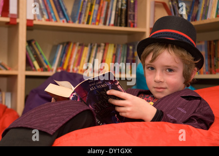 7 year old pupil reading in school library in costume for World Book Day 2014, Haslemere, Surrey, UK.
