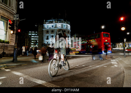 A cyclist balances on his bike as he waits at a red traffic light in Trafalgar Square. - Stock Photo