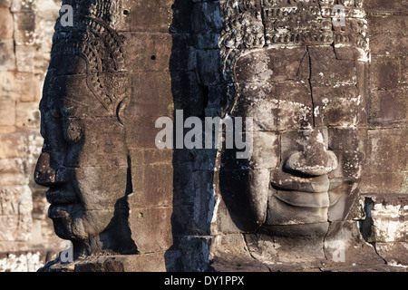 Two sculptured stone faces in Bayon Temple in Angkor near Siem Reap, Cambodia - Stock Photo