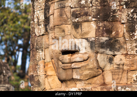 Smiling stone face in Bayon Temple in Angkor near Siem Reap, Cambodia - Stock Photo