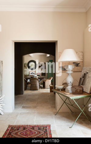 View From Salon Through To Dining Room With Stone Flooring A Lamp Sits On