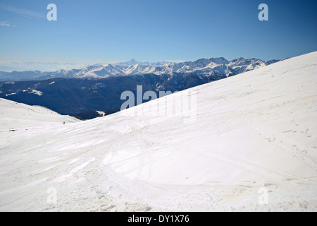 Infinite panoramic view from a snowy slope in spring with foggy valleys below. Unrecognizable tour skier. - Stock Photo