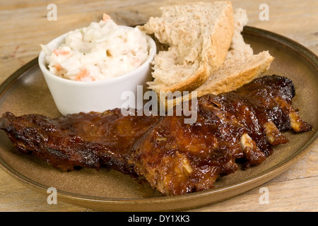 pork ribs in barbecue sauce with coleslaw and crusty bread - Stock Photo
