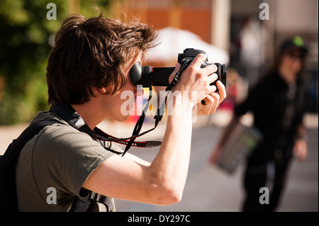 Man filming with a Canon DSLR camera, with his head close to the eye loupe - Stock Photo