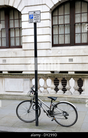 London, England, UK. Bicycle chained to a post in central London - Stock Photo