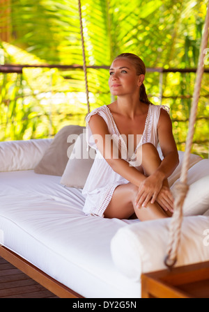 Beautiful girl sitting on swing in the beach house on Maldives, relaxation outdoors, luxury summer holidays in paradise - Stock Photo