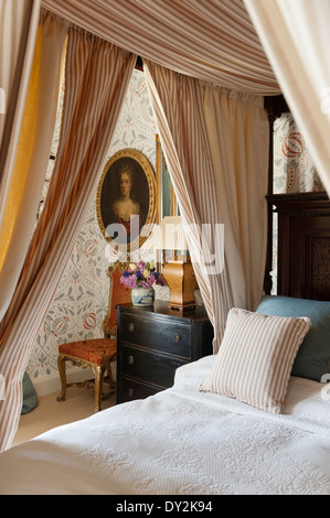 A four poster bed hung with striped Tulsi cotton from Malabar in bedroom with Chateau Sienna wallpaper by Lewis - Stock Photo