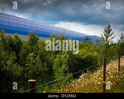 Exterior of Amazon UK warehouse in Rugeley Staffordshire England with stormy sky above and trees in foreground - Stock Photo