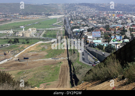Border fence separating the Mexican city of Mexicali on the right from the Imperial Valley of the United States - Stock Photo