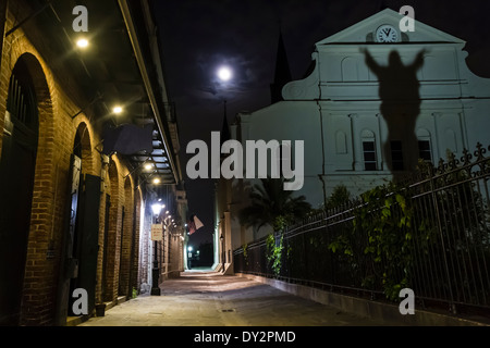 A full moon rises over Pere Antoine Alley and St. Anthony's Garden with a shadow on St. Louis Cathedral in New Orleans, - Stock Photo