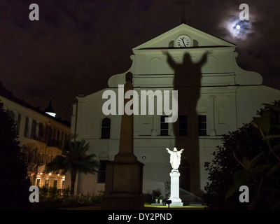 A full moon rises over St. Anthony's Garden with a shadow from the statue of Jesus  in the French Quarter of New - Stock Photo