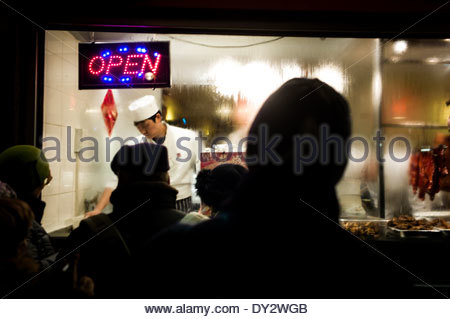 People watch a cook in Chinatown, part of the Soho area of the City of Westminster, occupying the area in and around - Stock Photo