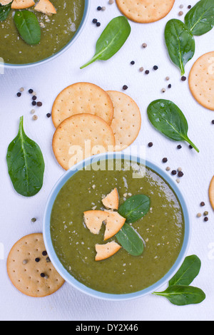 Spinach soup with crackers and black pepper shot from above - Stock Photo