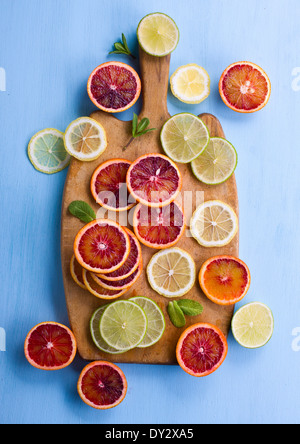 Assorted cut citrus fruits on cutting bord shot from above on light blue background - Stock Photo