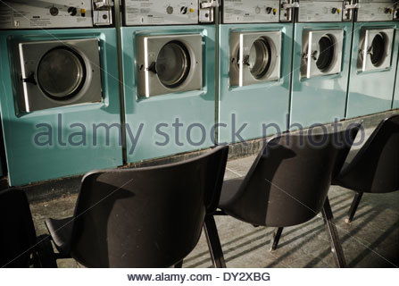 Interior of an empty launderette, with vacant seating opposite the washing machines. Stroud, UK. - Stock Photo
