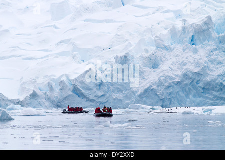 Antarctica tourism among the landscape of iceberg, glacier, and ice with tourists view penguins in zodiac. Antarctic Peninsula.