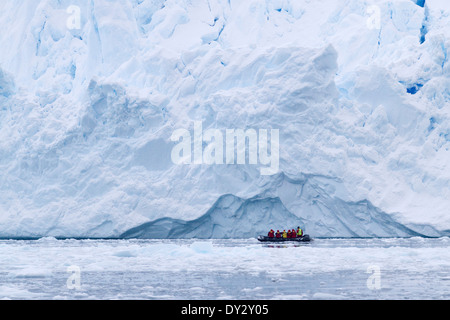 Antarctica tourism among the landscape of iceberg, glacier, and ice with tourists in zodiac. Antarctic Peninsula.