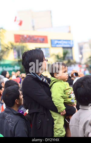 Unidentified woman holding a young child on the Wong Parade in Miraflores, Lima, Peru - Stock Photo