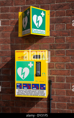 Defibrillator emergency life saving equipment mounted on a wall for public use, Overstrand, Norfolk, England - Stock Photo