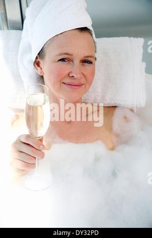 Mature woman enjoying bubble bath - Stock Photo