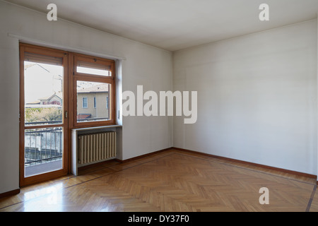 Empty room with wooden floor and dirty white walls - Stock Photo
