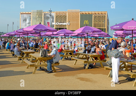 Picnic benches & parasols in London 2012 Olympic Park Paralympic games with temporary McDonalds restaurant beyond - Stock Photo