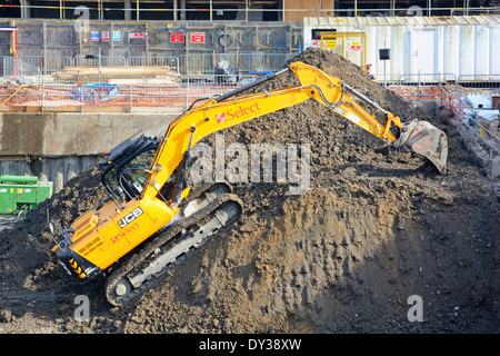 J.C. Bamford (JCB) tracked excavator & loader at work climbing back up to top of spoil heap on construction site - Stock Photo