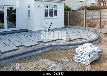 Paving slabs being laid as a patio to back garden of detached house after completion of rear extension - Stock Photo