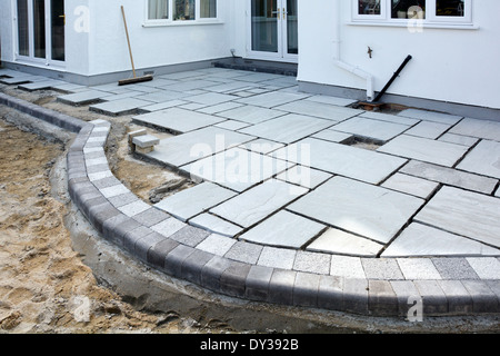 Paving slabs being laid as a patio to back garden of detached house after completion of rear extension Essex England - Stock Photo