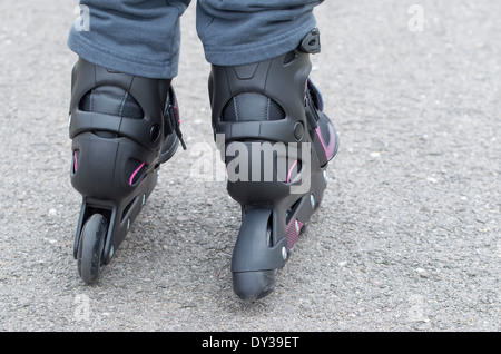 Foreground of inline skates, girl skating on the street - Stock Photo
