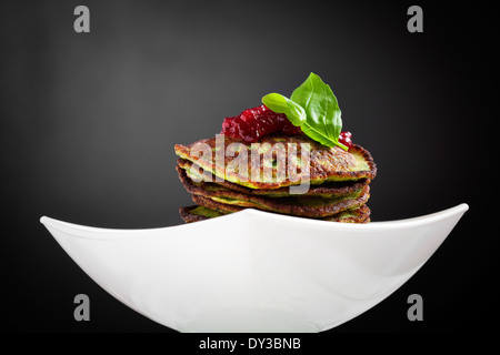 Healthy and delicious spinach pancakes with lingonberry jelly - Stock Photo