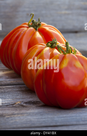 Three large Beefsteak Tomatoes in a Row fresh from the Weekly Market on a old wooden Table - Stock Photo