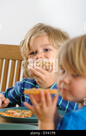 Two young boys enjoy a slice of pizza - Stock Photo