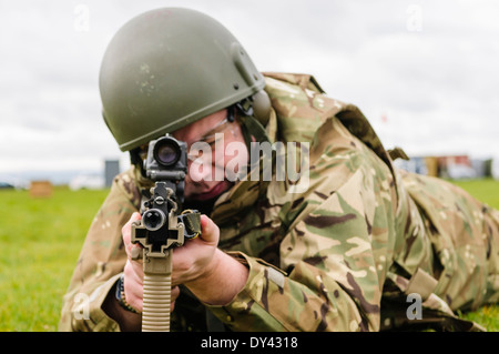 A British Army soldier lies prone on a firing range with a SA80 L85A2 assault rifle - Stock Photo