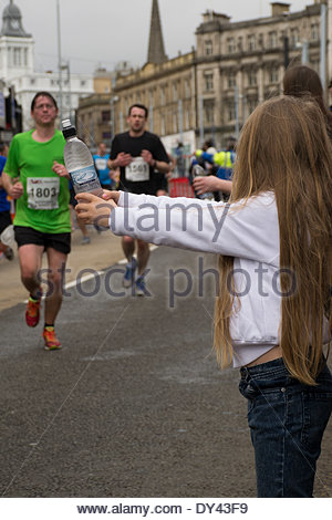 Sheffield, UK. 6th April, 2014. Spectators handing out bottles of water to runners in the Sheffield Half Marathon. - Stock Photo