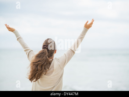 Young woman on cold beach rejoicing success. rear view - Stock Photo