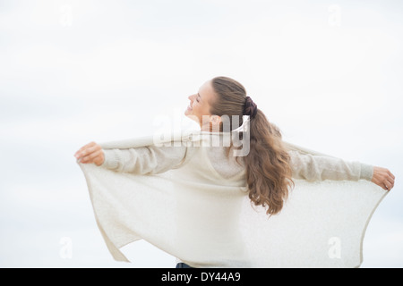 Young woman on cold beach rejoicing. rear view - Stock Photo