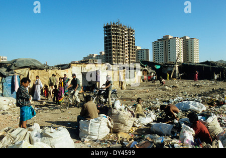 India Mumbai, slum and waste picker in Malad, background new apartment building, collecting plastic garbage for - Stock Photo