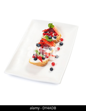 Profiteroles with berries currant strawberries and blueberries - Stock Photo