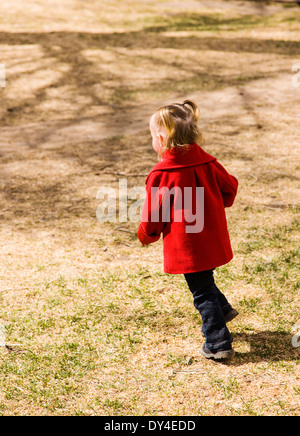 Adorable, cute 16 month little girl playing on a park playground - Stock Photo