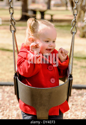 Adorable, cute 16 month little girl swinging on a park playground - Stock Photo