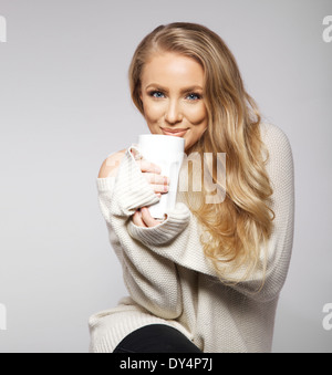 Cute smiling girl in oversized sweater. Lovely smiling young woman holding a cup of warm tea or coffee. - Stock Photo