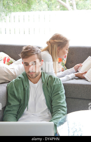 Man Using Laptop and Woman Reading Book on Sofa - Stock Photo