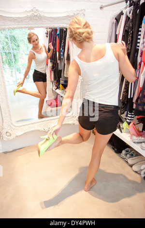 Woman in Closet Looking in Mirror Trying on Shoes - Stock Photo