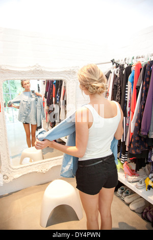 Woman in Closet Looking in Mirror Holding Shirt - Stock Photo