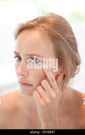 Concerned Woman Looking in Mirror Checking her Face