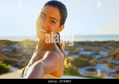 Smiling Young Woman with Arm Raised, Close-up View - Stock Photo
